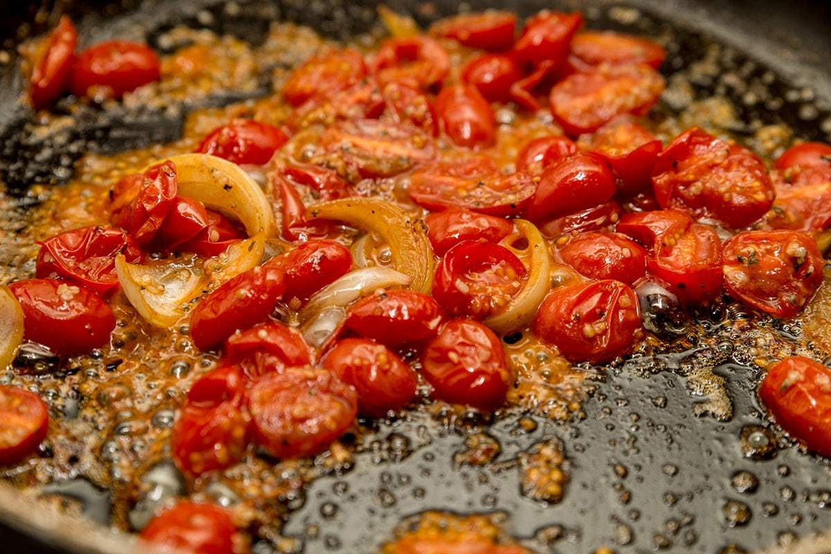 Tomatoes garlic and onions frying in the bottom of the pan